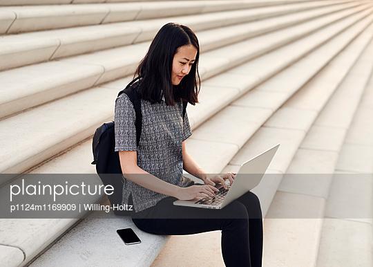 Asiatin sitzt mit Laptop und Smartphone auf Treppe - p1124m1169909 von Willing-Holtz