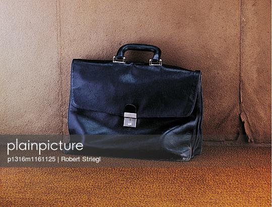 Aktentasche an einer Wand, Business, Arbeit - p1316m1161125 von Robert Striegl