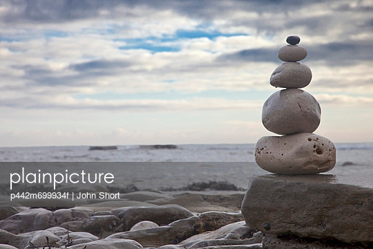 Pile of rocks balanced on a boulder at the water\'s edge; south shields tyne and wear england