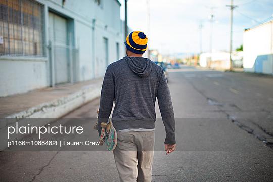 Man walking with skateboard along building
