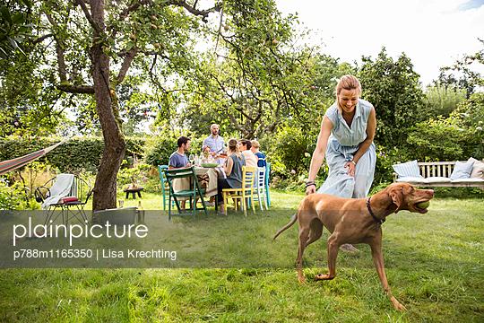 Frau spielt mit Hund im Garten - p788m1165350 von Lisa Krechting