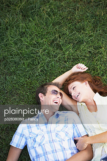 Happy Couple Lying Down in the Grass
