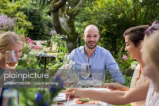 Freunde feiern eine Gartenparty - p788m1165306 von Lisa Krechting