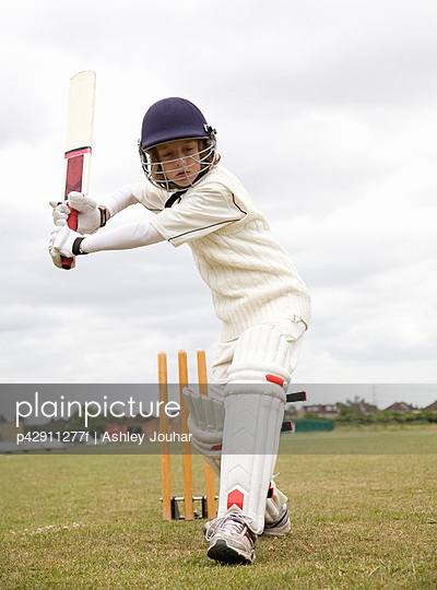 Boy (10-12) playing cricket