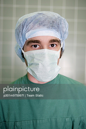 Surgeon wearing surgical mask and cap