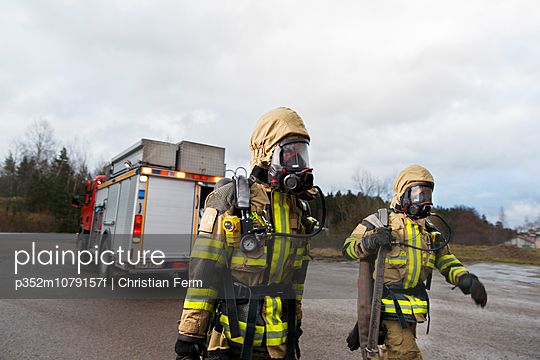 Sweden, Sodermanland, Tumba, Firefighters wearing gas mask walking on road