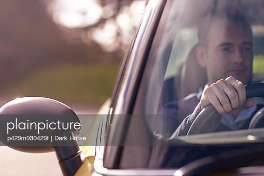 Man sitting behind wheel of car