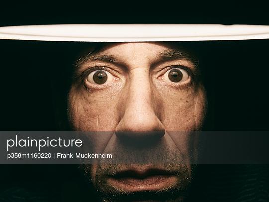 Männergesicht im Lampenschein - p358m1160220 von Frank Muckenheim