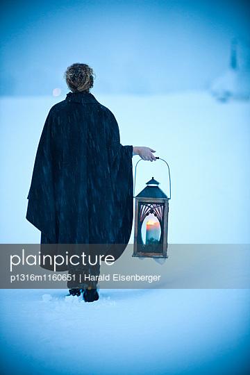 Frau mit einer Laterne geht durch Schnee, Steiermark, Österreich - p1316m1160651 von Harald Eisenberger