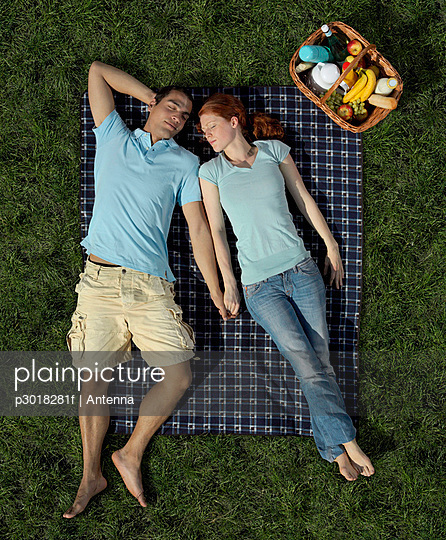 A young couple sleeping on a blanket in the park