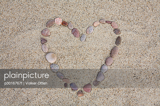 A heart shape made from pebbles on a beach