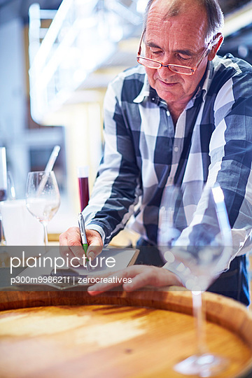 Wine tester writing on clipboard