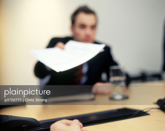 Businessman handing paper over conference table