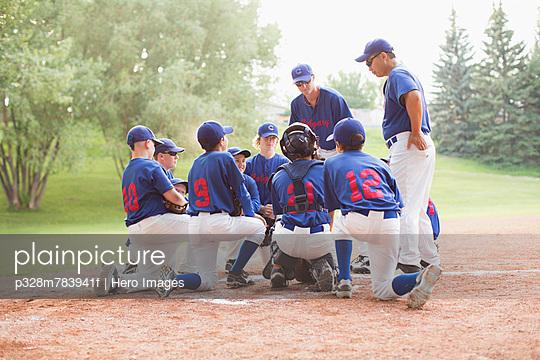 Coaches talking with boys baseball team.