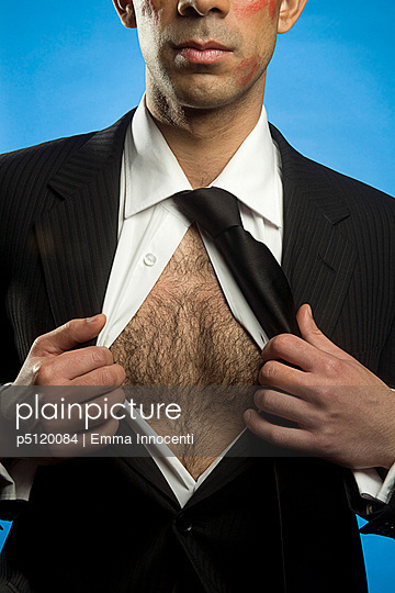 businessman in suit opening his shirt to reveal hairy chest