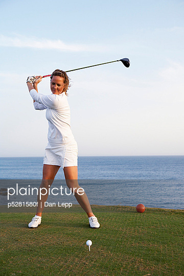 A woman playing golf by the sea Gran Canaria Spain