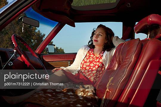 A pretty rockabilly woman sitting in the front seat of a vintage car