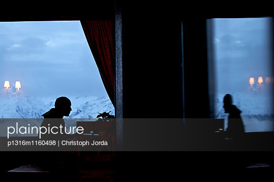 Mann sieht aus dem Fenster einer Herberge, Chandolin, Anniviers, Wallis, Schweiz - p1316m1160498 von Christoph Jorda