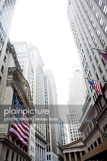 Low angle view of American flags and buildings on Wall Street at New York City, USA