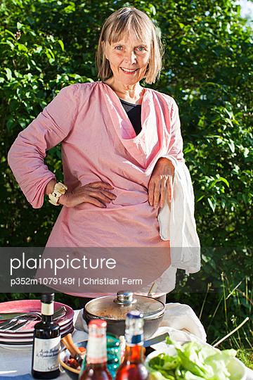 Sweden, Sodermanland, Jarna, Portrait of woman standing behind table in garden
