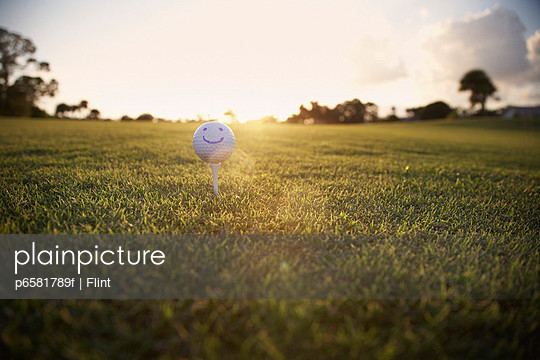 Golf Ball With Smiley Face on Tee