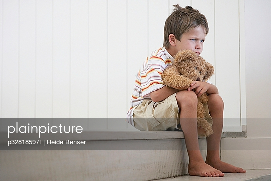 Sad young boy with a teddy bear
