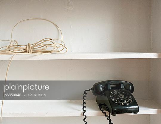 Black rotary telephone on shelf