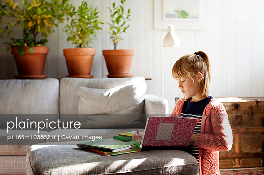 Girl (6-7) drawing in notebook in home interior