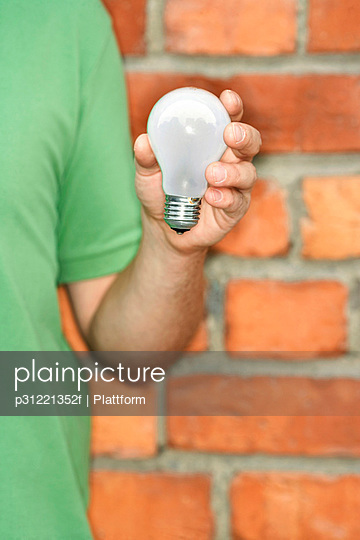 A man holding a light bulb for recycling.