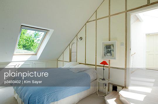 Light blue blanket on attic bed with sunlit skylight