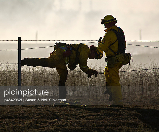 Firemen Climbing Through Wire Fence