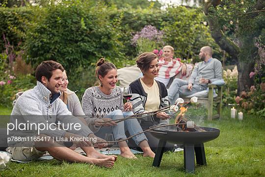 Freunde beim Marshmallows rösten - p788m1165417 von Lisa Krechting