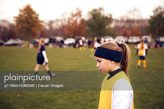 Sad girl (8-9) in playing field