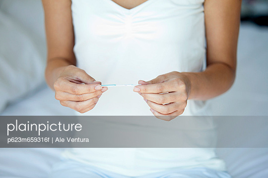 Woman holding pregnancy test, mid section