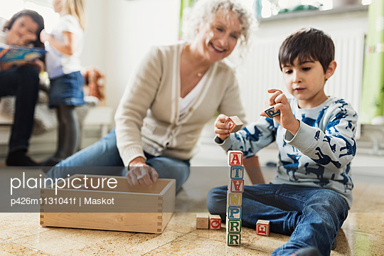 Happy teacher looking at boy stacking blocks at day care center