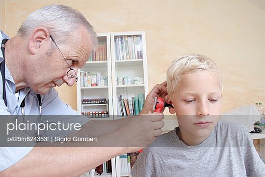 Doctor examining boy\'s ear