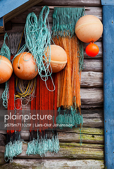 Buoys and fishing nets hanging on wooden wall