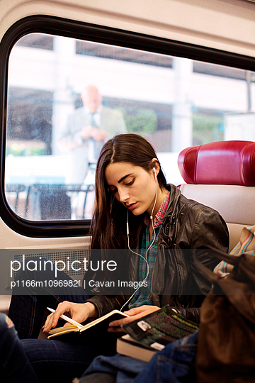 Young woman reading book while travelling in train