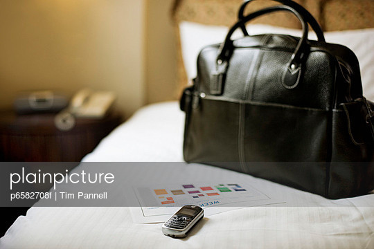 Travel Bag, Cell Phone and Newspaper on a Hotel Room Bed