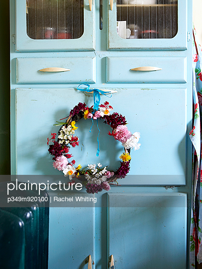Floral wreath on blue kitchen cabinet; Isle of Wight home; UK