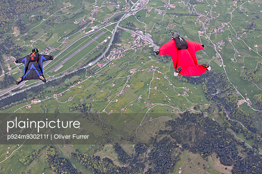 Two men flying above fields in wingsuits