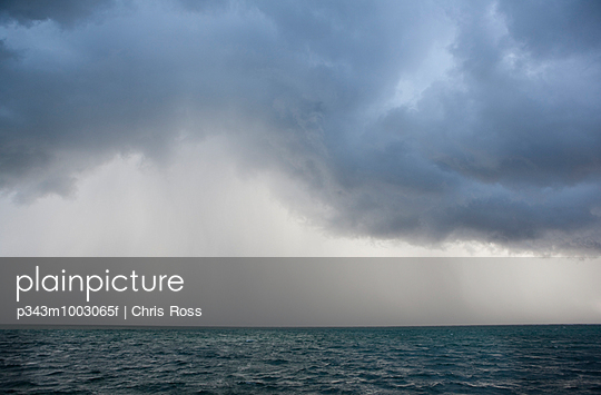 a view of an ocean storm with menacing clouds and rain showering below