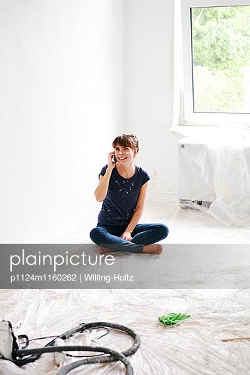 Frau telefoniert beim Renovieren - p1124m1160262 von Willing-Holtz