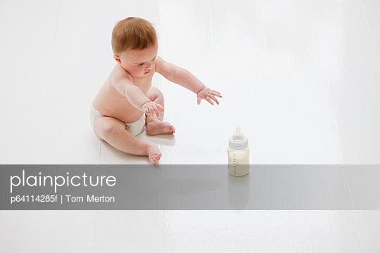 Baby on floor reaching for bottle of milk