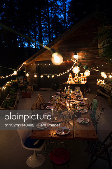 String lights illuminating food on dining table at night