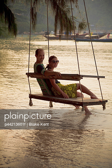 couple sits on beach swing at sunset; koh tao, thailand