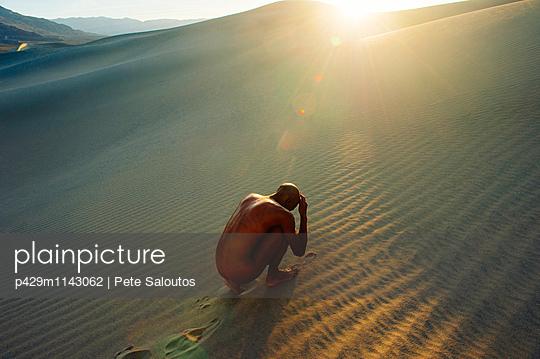 Nude woman cowering in desert