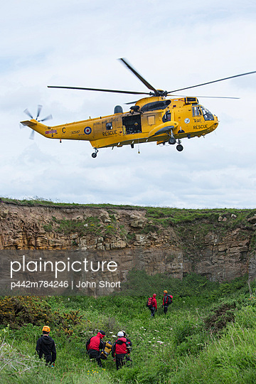 A Rescue Helicopter Flies Above Workers On The Ground; Northumberland England