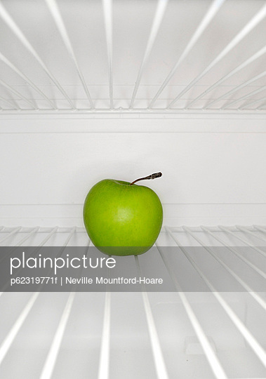 Single green apple sitting on shelf inside refrigerator
