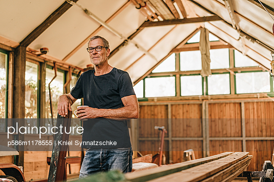 Mature man drinking coffee in workshop